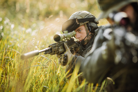 sniper training: military sniper shooting an assault rifle Stock Photo