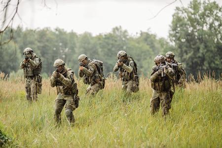 conflicto: grupo de soldados que se ejecutan a trav�s del campo y disparar Foto de archivo