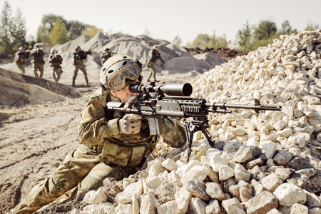 sniper training: Sniper covers offensive squad of rangers Stock Photo