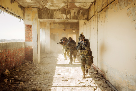 兵士は敵によって占められる建物を襲撃しました。 写真素材