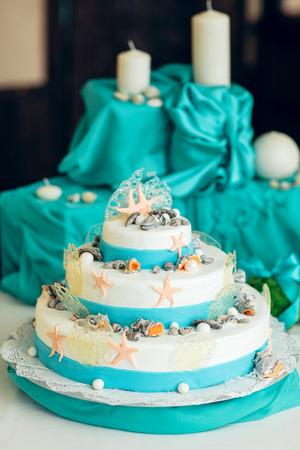 白と青のウェディング ケーキは貝殻で装飾されて