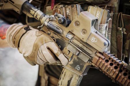 ranger in gloves holding assault automatic rifle Standard-Bild