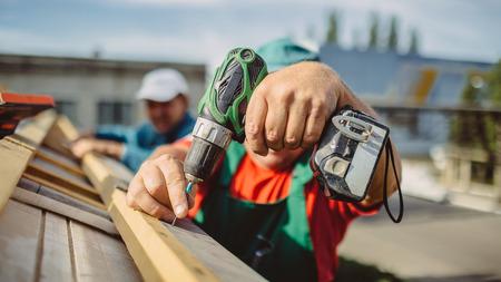 dakdekker met een boor is het bevestigen van een cap naar een nieuw huis dak Stockfoto