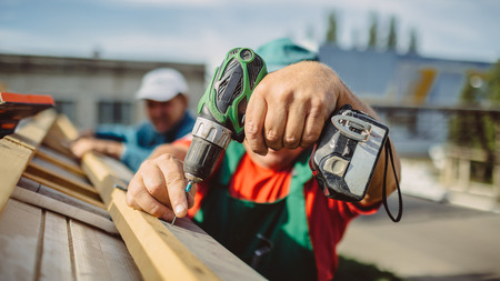 roof house: roofer using a drill is fastening a cap to a new house roof Stock Photo