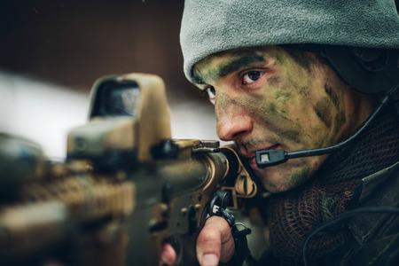 fusil de chasse: homme armé en tenue de camouflage avec des armes à feu dans les mains sniper