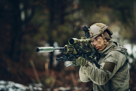armed  man in camouflage with sniper gun in hands
