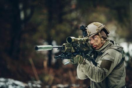 hombre disparando: hombre armado en camuflaje con el arma de francotirador en manos