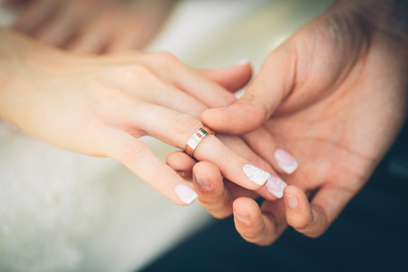 A grooms hand and a brides hand with a ring