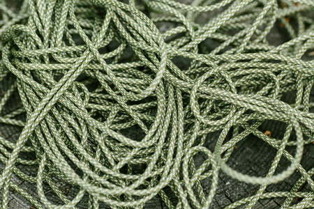 mess: Mess green rope against wood background
