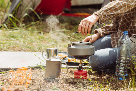 A person boiling water in a pot over a propane stove to make tea