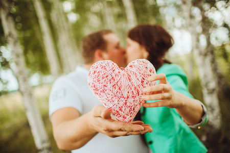 jointly: Happy and young couple in love kissing and holding a heart in a birch grove