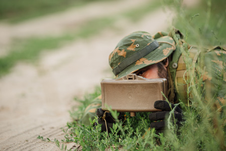 detecting: soldiers set mine in the grass next to the road