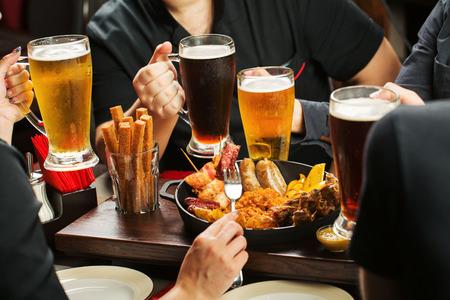 botanas: Manos que sostienen cuatro vasos de cerveza que beben junto en el pub