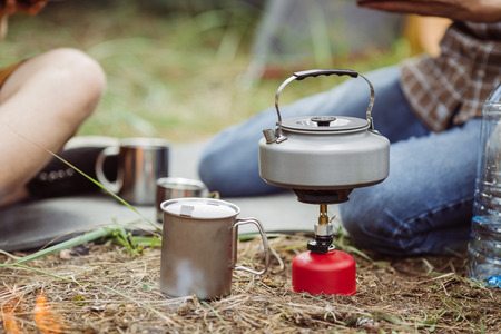 A camping tea kettle on a propane stove next to a metal cup