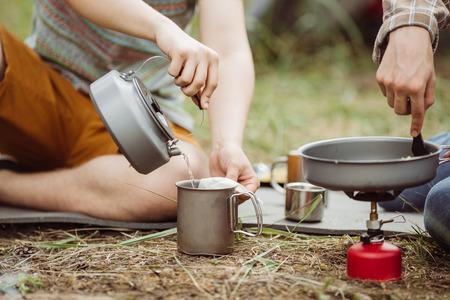 campamento: Dos compañeros campistas set de té y la preparación de alimentos en el bosque