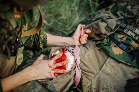 female military doctor to help the wounded soldier Stockfoto