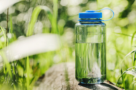 fresh water: Water bottle on wood  with summer scene background