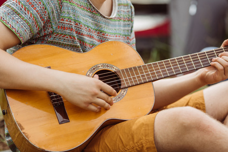 young tourist sitting in the tent, play the guitar and sing songs