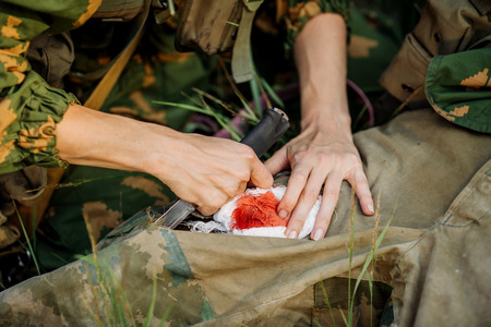 hurt: female military doctor to help the wounded soldier Stock Photo