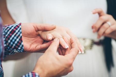 A close up of a groom gently holding a gold ring on his brides hand