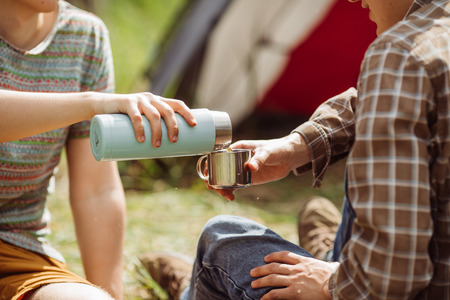 A person pouring tea from a tumbler into his friends cup while camping
