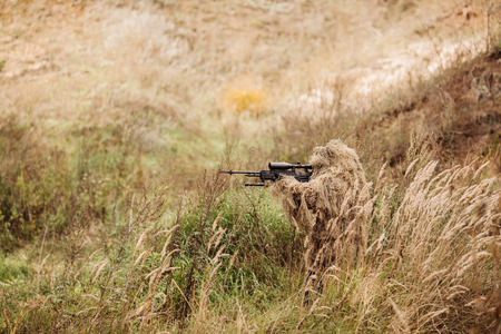 A camouflaged sniper sitting in the field aiming through his scope