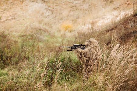 Eine getarnte sniper auf dem Gebiet sitzt durch seinen Bereich Ziel Lizenzfreie Bilder