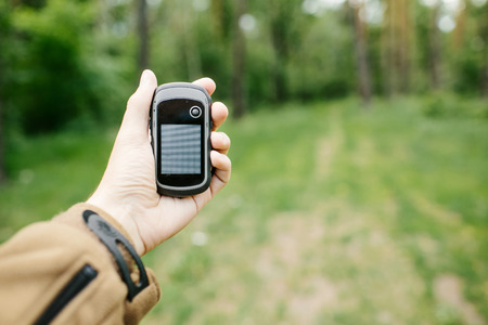 predominantly: Man holding a GPS receiver and plan in his hand. Handheld GPS devices are used predominantly in the outdoor leisure industry for walking and hiking. Stock Photo