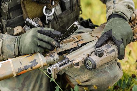 Ranger Reparatur beheben das Gewehr mit dem Werkzeug auf dem Schlachtfeld Standard-Bild - 42658917