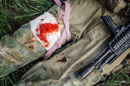 負傷した兵士の腕を草の上に横たわる