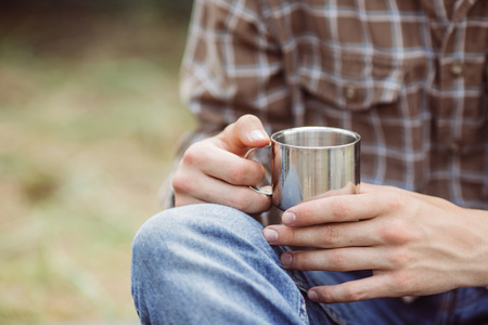 キャンプしながらお茶のチタンのカップを保持している人 写真素材