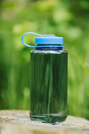 夏のシーンの背景の木の上の水のボトル