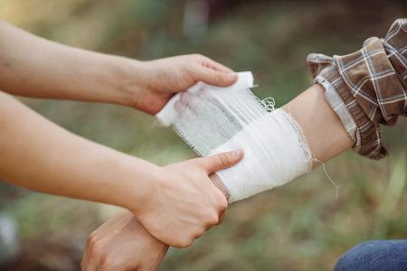 lesionado: Una persona envolviendo sus amigos lesionó el brazo en gasa