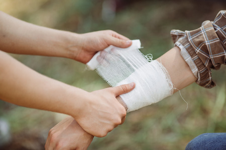 A person wrapping his friends injured arm in gauze