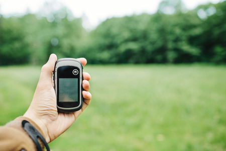 Man holding a GPS receiver and plan in his hand. Handheld GPS devices are used predominantly in the outdoor leisure industry for walking and hiking. Standard-Bild