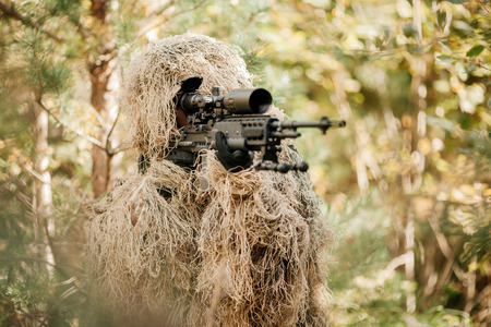 A camouflaged sniper sitting in the woods aiming through his scope