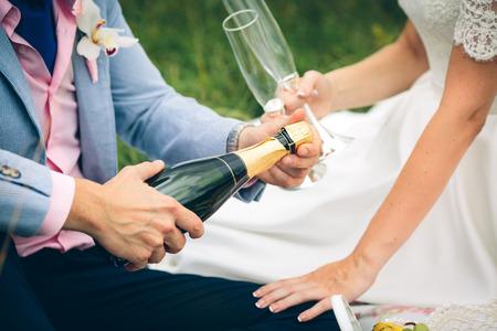 Bräutigam öffnet eine grüne Flasche Champagner