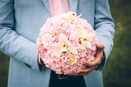 新郎の手にピンクの花のウェディング ブーケ