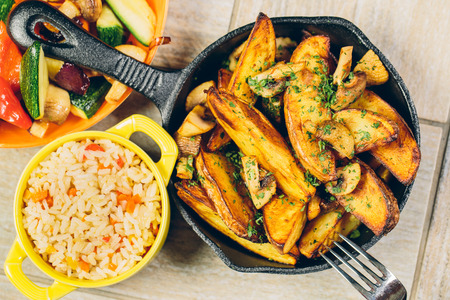 A frying pan of baked potatos with a bowl of rice and vegetables Reklamní fotografie