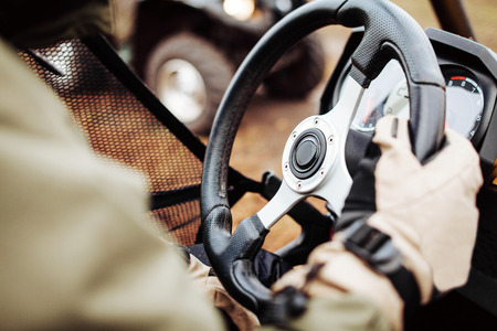 atv: ATV driver holds the steering wheel with gloves
