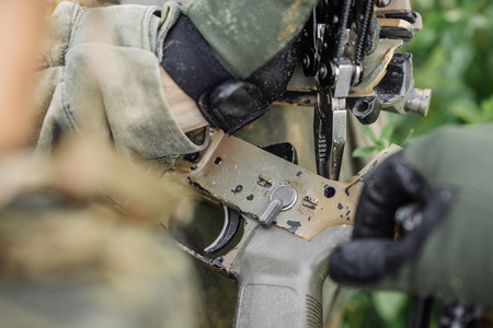 finger on trigger: ranger repair fix the rifle with the tool in the battlefield Stock Photo