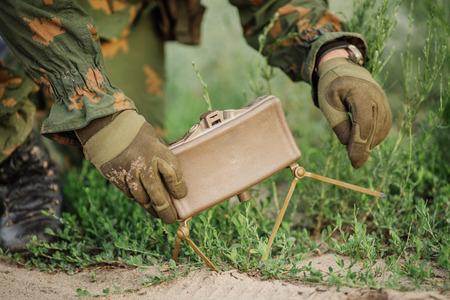 兵士は、道路の横にある草の中に地雷を設定します。