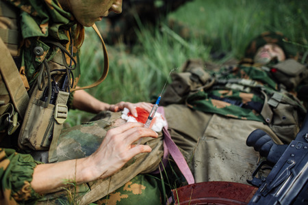 female military doctor to help the wounded soldier Reklamní fotografie