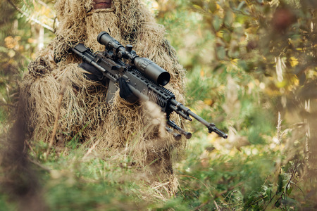 A camouflaged sniper with a rifle sitting in the woods waiting