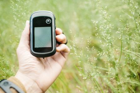 Man hält ein GPS-Empfänger und Plan in der Hand. Handheld-GPS-Geräte werden vorwiegend in der Outdoor-Freizeitindustrie zum Spazieren und Wandern verwendet.