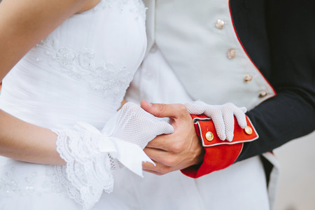 hussar: A groom in a hussar uniform gently holding his wifes hand