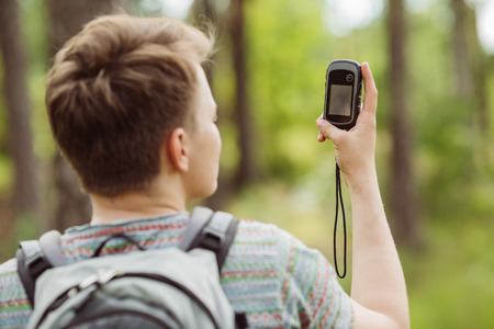 determines: young tourist  in the woods determines location using gps