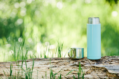 thermos: Water bottle on wood  with summer scene background