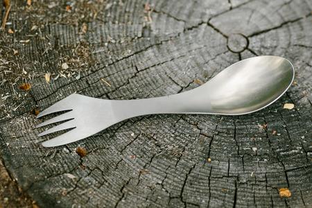 titanium spork lying on a wooden stump in the forest Standard-Bild