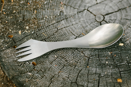 bivouac: titanium spork lying on a wooden stump in the forest Stock Photo